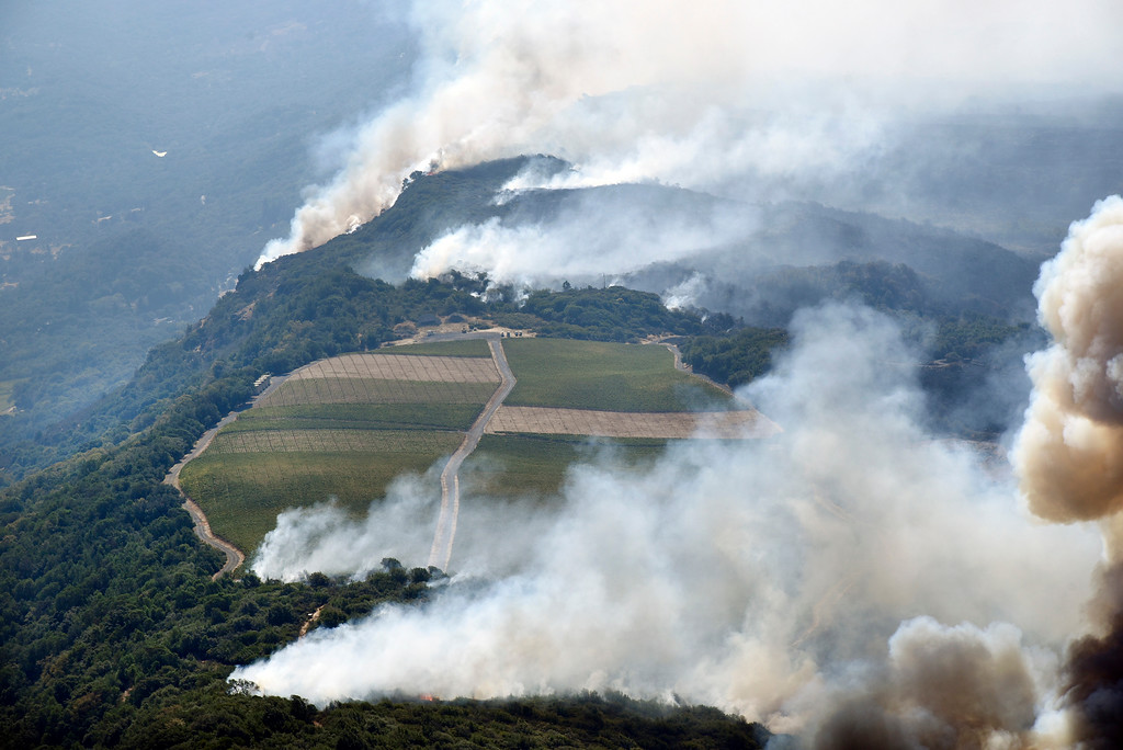 . Smoke rises as a wildfire burns in the hills north east of Napa, Calif., Monday, Oct. 9, 2017. Wildfires whipped by powerful winds swept through Northern California sending residents on a headlong flight to safety through smoke and flames as homes burned. (Michael Short/San Francisco Chronicle via AP)