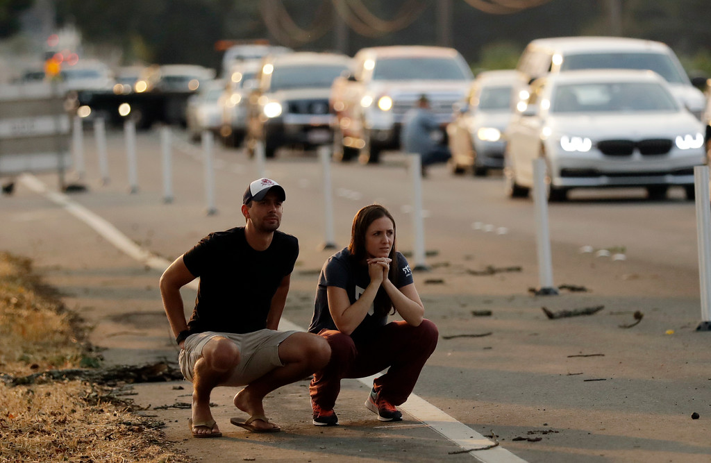 . Drew Casey, left, and his fiancee Lauren Foster watch a wildfire from a road closure Monday, Oct. 9, 2017, in Napa, Calif. (AP Photo/Marcio Jose Sanchez)