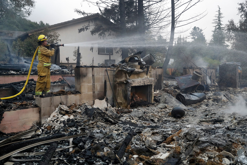 . Napa City firefighter Hattie Borg hoses down a fire-ravaged home Monday, Oct. 9, 2017, in Napa, Calif. (AP Photo/Marcio Jose Sanchez)