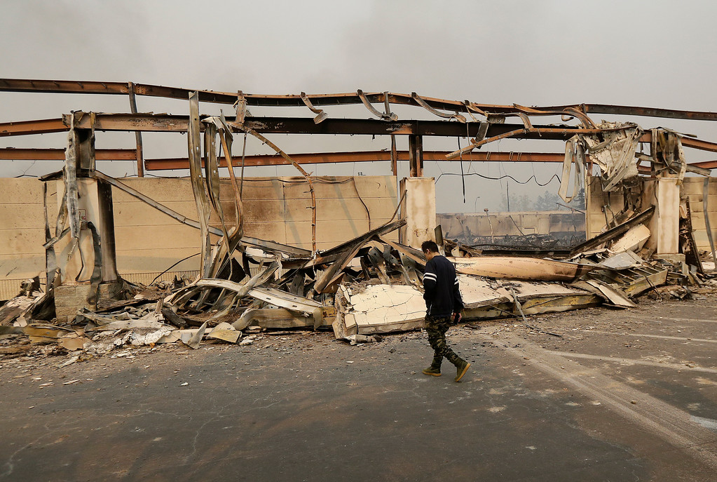 . A man walks past the front of a Kmart store destroyed by a fire in Santa Rosa, Calif., Monday, Oct. 9, 2017. Wildfires whipped by powerful winds swept through Northern California early Monday, sending residents on a headlong flight to safety through smoke and flames as homes burned. (AP Photo/Jeff Chiu)