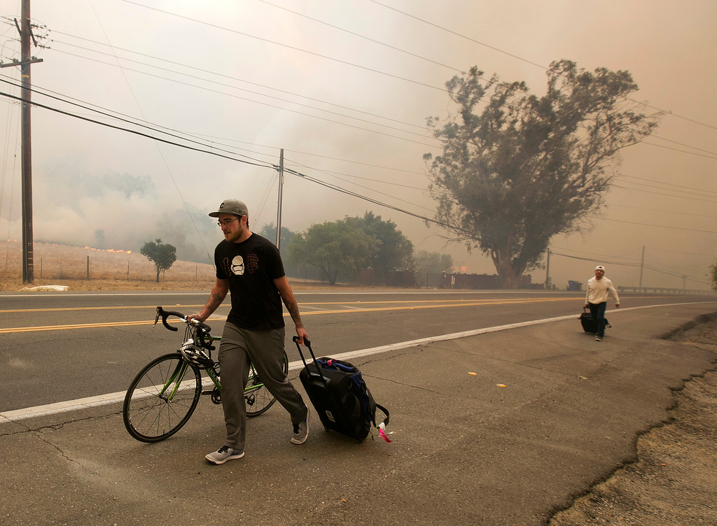 . Area residents evacuate as flames from a massive wildfire approach their homes Monday, Oct. 9, 2017, in Napa, Calif. (AP Photo/Rich Pedroncelli)