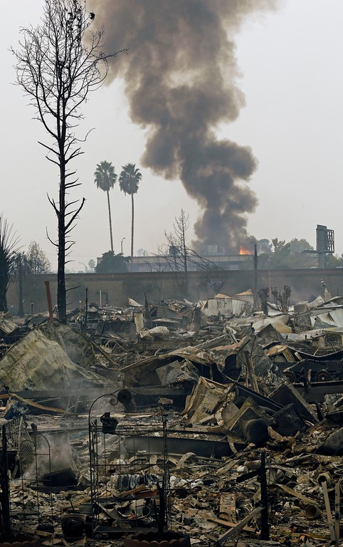 . Fire burns a business as viewed from the demolished Journey\'s End mobile home park Monday, Oct. 9, 2017, in Santa Rosa, Calif. Wildfires whipped by powerful winds swept through Northern California early Monday, sending residents on a headlong flight to safety through smoke and flames as homes burned. (AP Photo/Ben Margot)