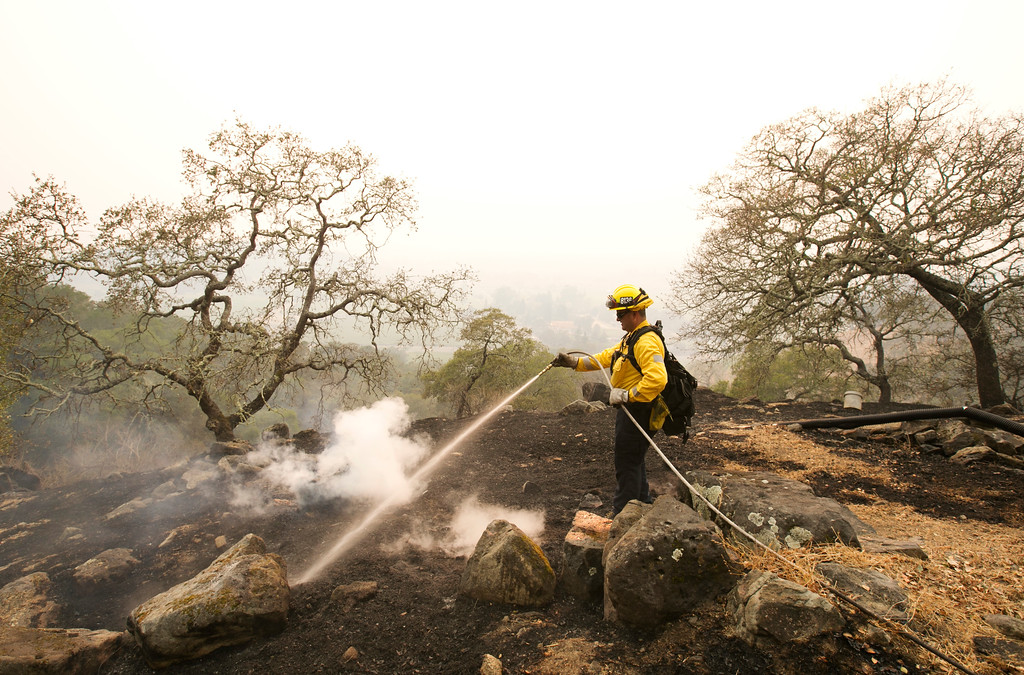 . Firefighter Luis Ochoa, of the Los Angeles City Fire Department, hoses down a hotspot from a wildfire that swept through the area, Monday, Oct. 9, 2017, in Napa, Calif. Wildfires whipped by powerful winds swept through Northern California sending resident on a headlong flight to safety through smoke and flames as homes burned. (AP Photo/Rich Pedroncelli)