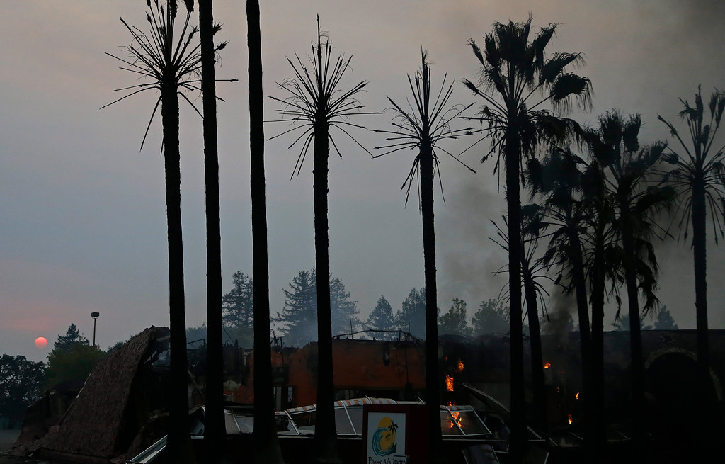 . Fires smolder in a business as the sun sets Monday, Oct. 9, 2017, in Santa Rosa, Calif. Wildfires whipped by powerful winds swept through Northern California early Monday, sending residents on a headlong flight to safety through smoke and flames as homes burned. (AP Photo/Ben Margot)