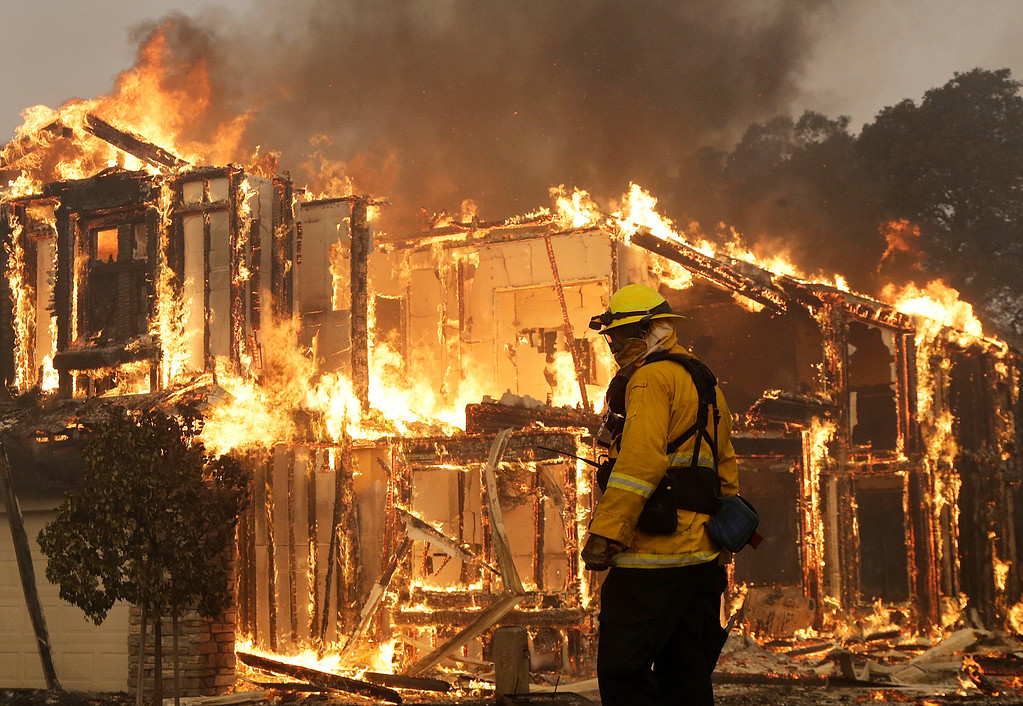 . A firefighter monitors a house burning in Santa Rosa, Calif., Monday, Oct. 9, 2017.  Wildfires whipped by powerful winds swept through Northern California sending residents on a headlong flight to safety through smoke and flames as homes burned. (AP Photo/Jeff Chiu)