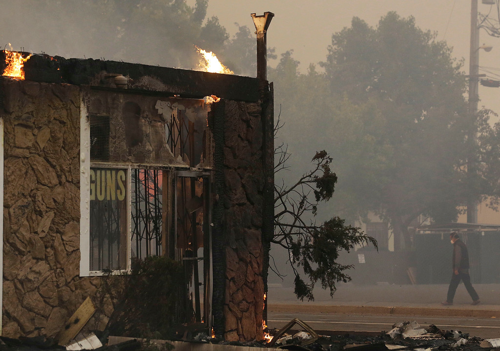 . Flames burn from the roof of a gun shop that caught fire in Santa Rosa, Calif., Monday, Oct. 9, 2017. Wildfires whipped by powerful winds swept through Northern California sending residents on a headlong flight to safety through smoke and flames as homes burned. (AP Photo/Jeff Chiu)