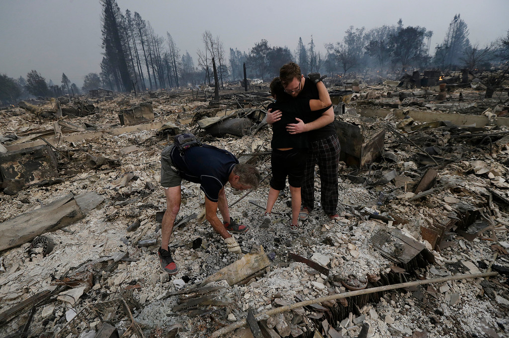 . Michael Pond, left, looks through ashes as his wife Kristine, center, gets a hug from Zack Thurston, their daughter\'s boyfriend, while they search the remains of their home destroyed by fires in Santa Rosa, Calif., Monday, Oct. 9, 2017. (AP Photo/Jeff Chiu)