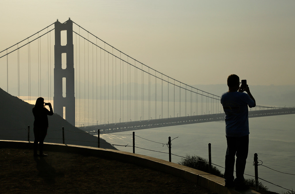 . People take pictures of the Golden Gate Bridge as smoke from wildfires covers the San Francisco skyline Tuesday, Oct. 10, 2017, in this view near Sausalito, Calif. An onslaught of wildfires across a wide swath of Northern California broke out almost simultaneously then grew exponentially, swallowing up properties from wineries to trailer parks and tearing through both tiny rural towns and urban subdivisions. (AP Photo/Eric Risberg)
