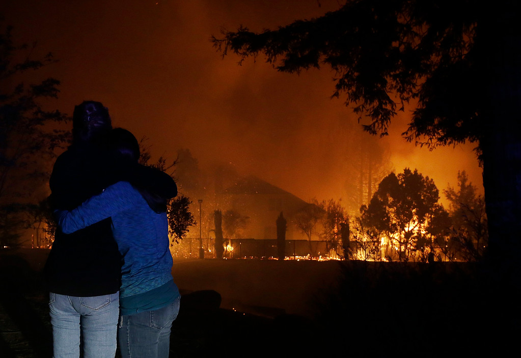 . Two women hug as they watch houses burn in Santa Rosa, Calif., Monday, Oct. 9, 2017. (AP Photo/Jeff Chiu)