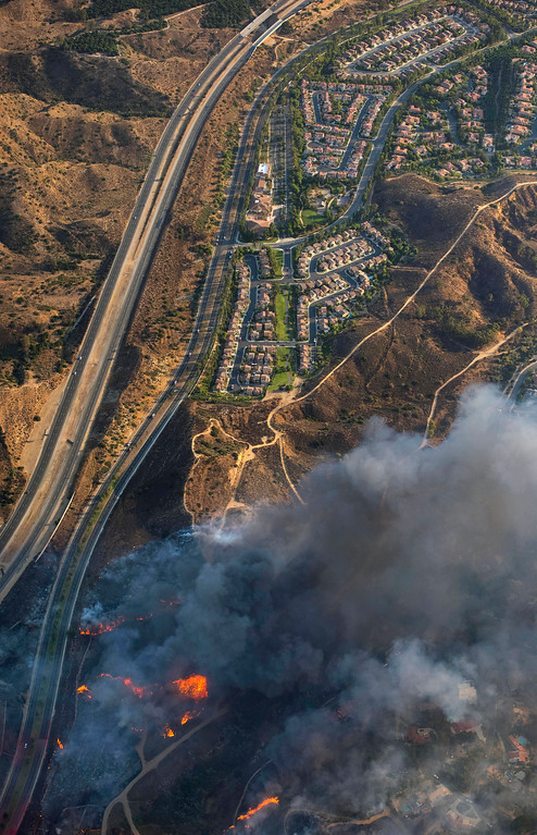 . A wildfire moves closer to North Tustin homes along the 261 freeway in Tustin, Calif., Monday, Oct. 9, 2017. Deadly wildfires whipped by powerful winds swept through California wine country Monday, destroying 1,500 homes and businesses and sending thousands fleeing as flames raged unchecked through high-end resorts, grocery stores and tree-lined neighborhoods. (Cindy Yamanaka/The Orange County Register via AP)