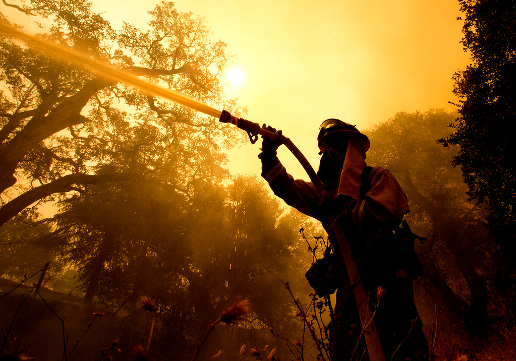 . Napa County firefighter Jason Sheumann sprays water on a home as he battles flames from a wildfire Monday, Oct. 9, 2017, in Napa, Calif. Wildfires whipped by powerful winds swept through Northern California sending residents on a headlong flight to safety through smoke and flames as homes burned. (AP Photo/Rich Pedroncelli)