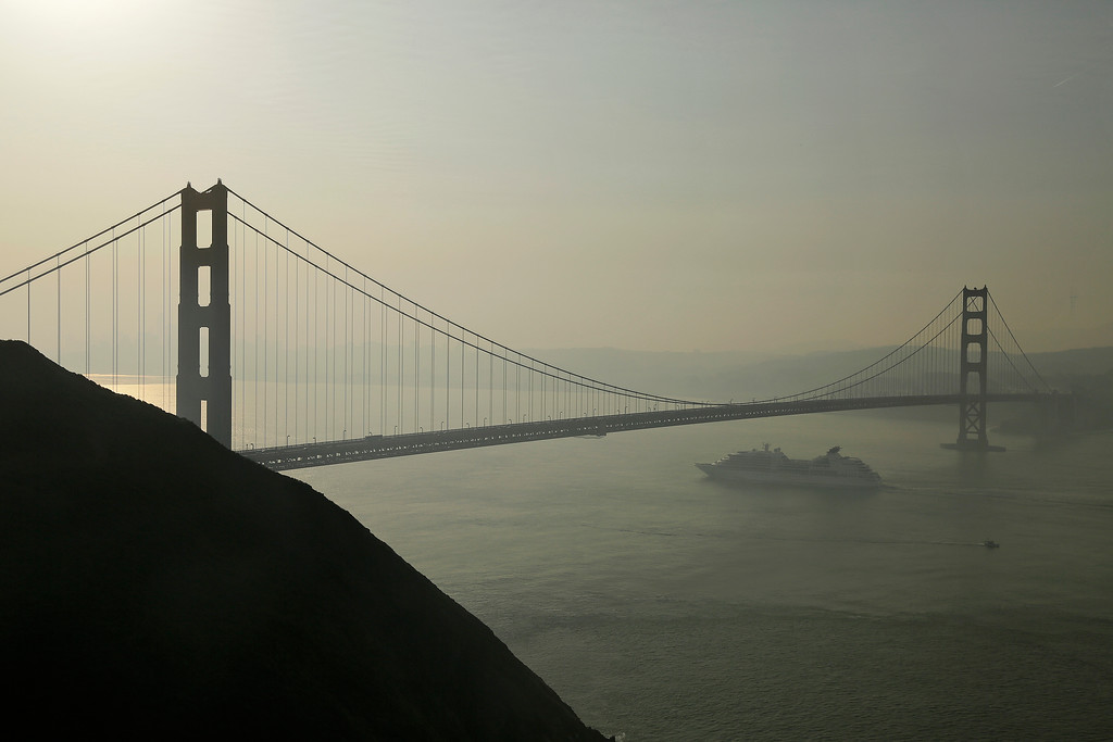 . A cruise ship passes beneath the Golden Gate Bridge as smoke from wildfires blankets the San Francisco skyline Tuesday, Oct. 10, 2017, in this view near Sausalito, Calif. An onslaught of wildfires across a wide swath of Northern California broke out almost simultaneously then grew exponentially, swallowing up properties from wineries to trailer parks and tearing through both tiny rural towns and urban subdivisions. (AP Photo/Eric Risberg)