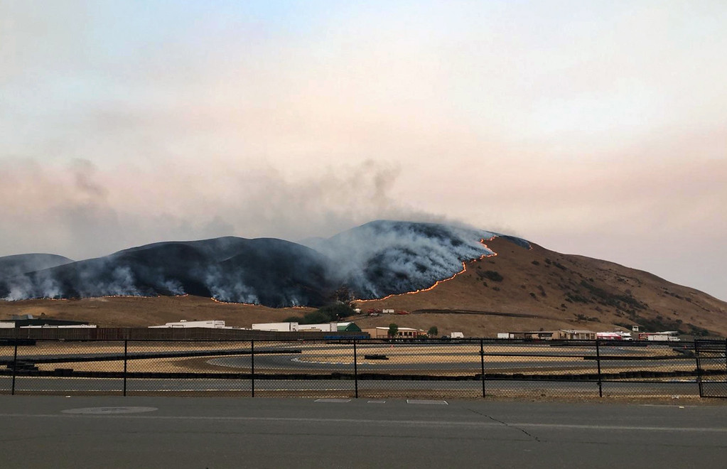 . In this photo provided by the Sonoma Raceway, a wildfire burns behind the Sonoma Raceway on Monday, Oct. 9, 2017, in Sonoma, Calif. Wildfires whipped by powerful winds swept through Northern California early Monday, sending residents on a headlong flight to safety through smoke and flames as homes burned.  (Steve Page/Sonoma Raceway via AP)