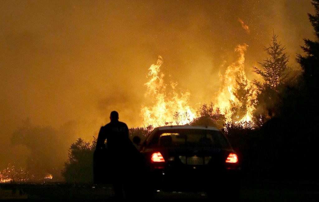 . A law enforcement officer blocks a road as flames from a wildfire burn in a residential area in Santa Rosa, Calif., Monday, Oct. 9, 2017. (AP Photo/Jeff Chiu)