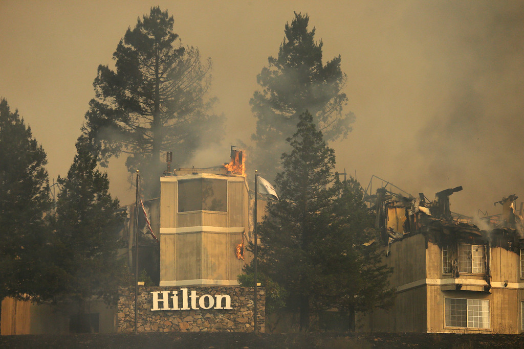 . Fire burns a Hilton hotel on Monday, Oct. 9, 2017, in Santa Rosa, Calif. Wildfires whipped by powerful winds swept through Northern California, sending residents on a headlong flight to safety through smoke and flames as homes burned. (AP Photo/Ben Margot)