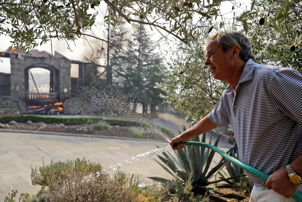 . Wirt Cook uses a hose to ward embers off his home as a neighbor\'s house burns Monday, Oct. 9, 2017, in Napa, Calif. Wildfires whipped by powerful winds swept through Northern California sending residents on a headlong flight to safety through smoke and flames as homes burned.  (AP Photo/Marcio Jose Sanchez)