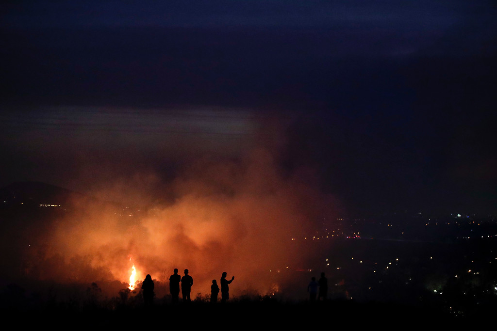. People watch as a wildfire burns along a hillside Monday, Oct. 9, 2017, in Orange, Calif. Authorities say at least half a dozen homes have burned in a fast-moving brush fire in Southern California. (AP Photo/Jae C. Hong)