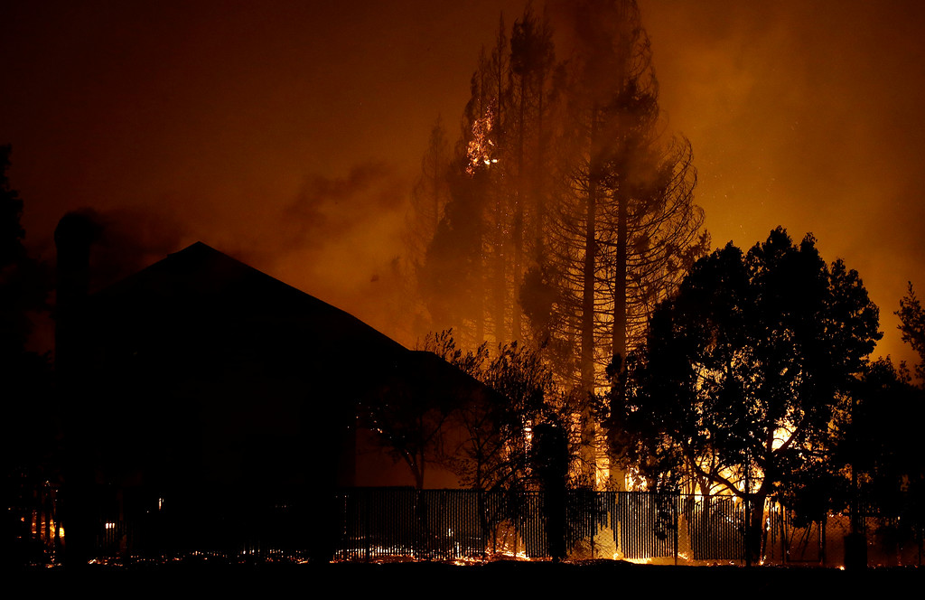 . Trees burn behind houses in a residential area in Santa Rosa, Calif., Monday, Oct. 9, 2017. (AP Photo/Jeff Chiu)