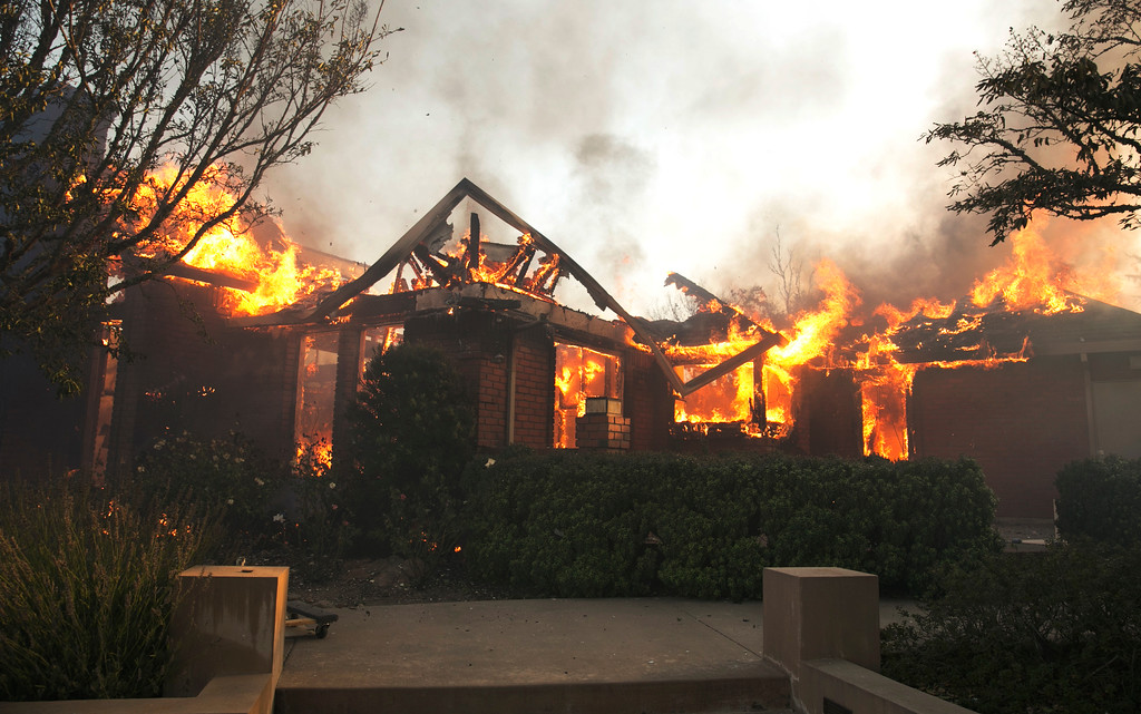 . Flames from a wildfire consume a home Monday, Oct. 9, 2017, east of Napa, Calif. Wildfires whipped by powerful winds swept through Northern California early Monday, sending residents on a headlong flight to safety through smoke and flames as homes burned. (AP Photo/Rich Pedroncelli)
