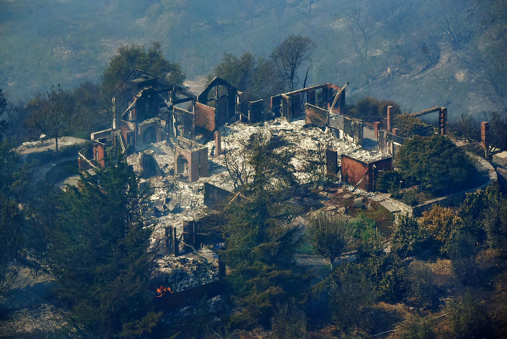 . Smoke rises from a home that was destroyed by a wildfire near Monticello Road in the hills east of Napa, Calif., Monday, Oct. 9, 2017. Wildfires whipped by powerful winds swept through Northern California sending residents on a headlong flight to safety through smoke and flames as homes burned. (Michael Short/San Francisco Chronicle via AP)