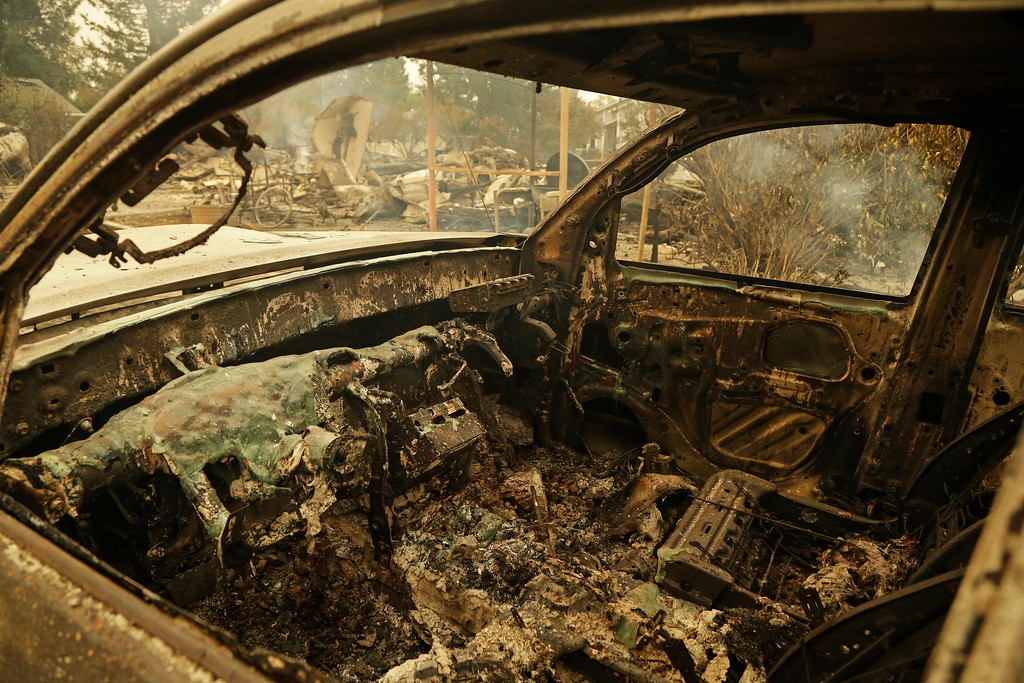 . The remains of an automobile sit in the Coffey Park area of Santa Rosa, Calif. An onslaught of wildfires across a wide swath of Northern California broke out almost simultaneously then grew exponentially, swallowing up properties from wineries to trailer parks and tearing through both tiny rural towns and urban subdivisions. (AP Photo/Ben Margot)