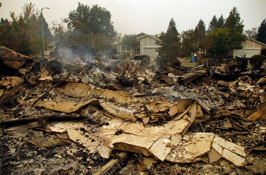 . Smoke raises from the remains of homes across the street from houses unscathed on Tuesday, Oct. 10, 2017, in the Coffey Park area of Santa Rosa, Calif. An onslaught of wildfires across a wide swath of Northern California broke out almost simultaneously then grew exponentially, swallowing up properties from wineries to trailer parks and tearing through both tiny rural towns and urban subdivisions. (AP Photo/Ben Margot)