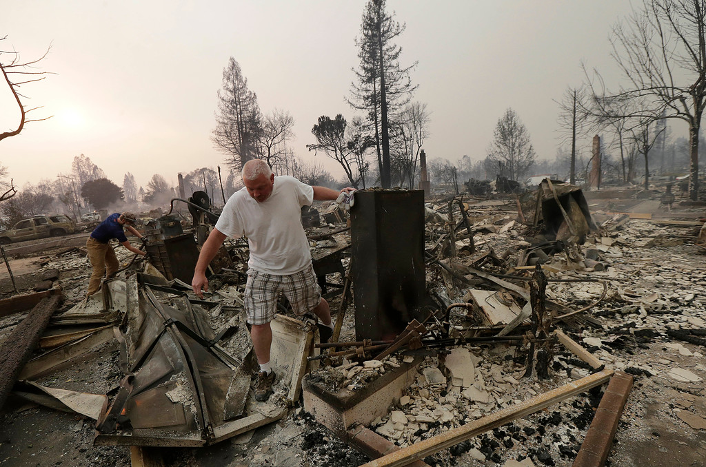 . Mark Pedersen and his son Ben, left, look through the remains of their home destroyed by fires in Santa Rosa, Calif., Monday, Oct. 9, 2017. (AP Photo/Jeff Chiu)