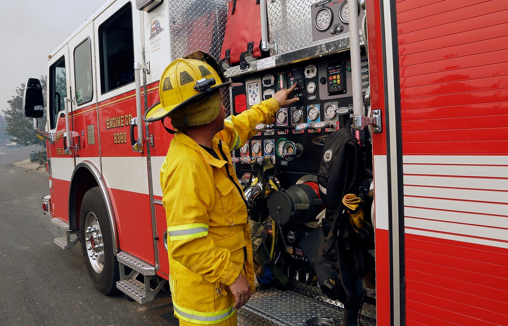 . A fireman checks gauges on a fire truck on Monday, Oct. 9, 2017, in Santa Rosa, Calif. Wildfires whipped by powerful winds swept through Northern California early Monday, sending residents on a headlong flight to safety through smoke and flames as homes burned. (AP Photo/Ben Margot)
