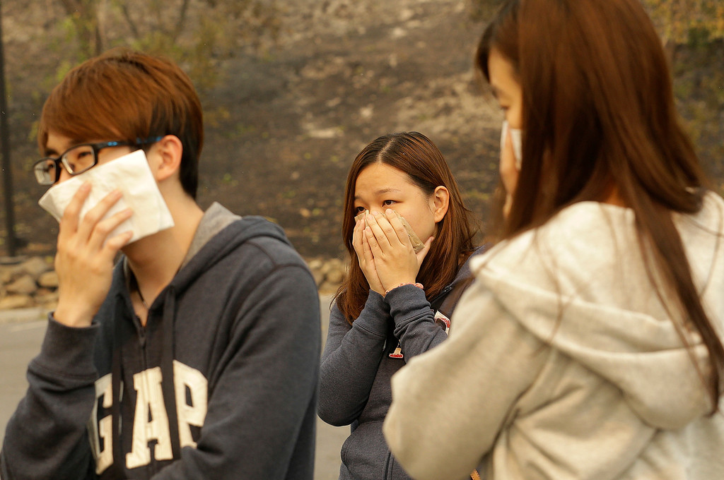 . Vincent Yeoh, from left, Ai Peng, Estella Fong, all from Malaysia, cover their mouths from smoke coming from a burning Hilton Sonoma Wine Country hotel, where they were all staying, in Santa Rosa, Calif., Monday, Oct. 9, 2017. Wildfires whipped by powerful winds swept through Northern California early Monday, sending residents on a headlong flight to safety through smoke and flames as homes burned. (AP Photo/Jeff Chiu)