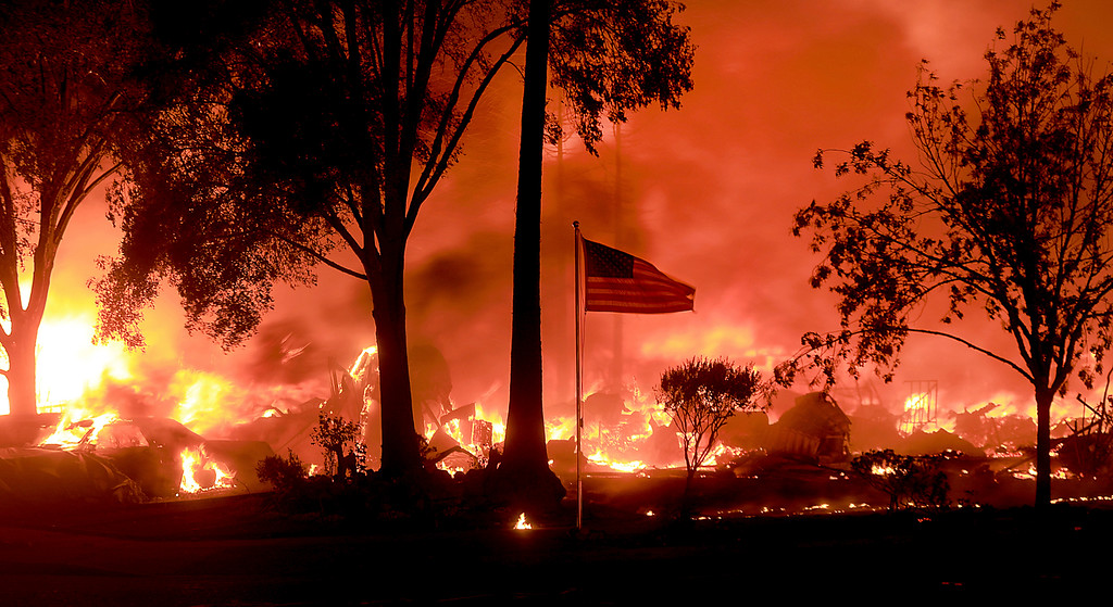 . An American flag still fly\'s as as structures burn in Coffey Park, Monday Oct. 9, 2017. More than a dozen wildfires whipped by powerful winds been burning though California wine country. The flames have destroyed at least 1,500 homes and businesses and sent thousands of people fleeing. (Kent Porter/The Press Democrat via AP)