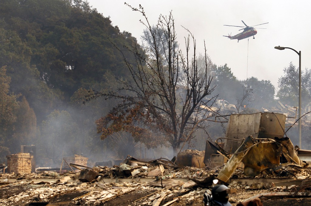 . A helicopter drops water in the Fountaingrove area on Monday, Oct. 9, 2017, in Santa Rosa, Calif. Wildfires whipped by powerful winds swept through Northern California early Monday, sending residents on a headlong flight to safety through smoke and flames as homes burned. (AP Photo/Ben Margot)