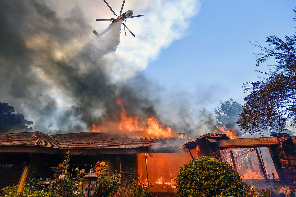 . A helicopter dumps water on a home as firefighters battle a wildfire in Anaheim Hills in Anaheim, Calif., Monday, Oct. 9, 2017. Wildfires whipped by powerful winds swept through Northern California sending residents on a headlong flight to safety through smoke and flames as homes burned. (Jeff Gritchen/The Orange County Register via AP)