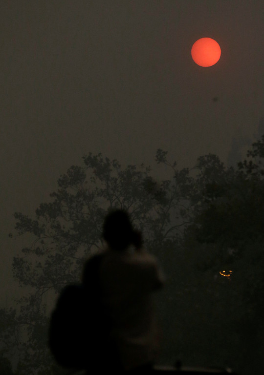 . A woman takes a photo of the sun covered from smoke and haze from fires in Santa Rosa, Calif., Monday, Oct. 9, 2017. Wildfires whipped by powerful winds swept through Northern California early Monday, sending residents on a headlong flight to safety through smoke and flames as homes burned. (AP Photo/Jeff Chiu)
