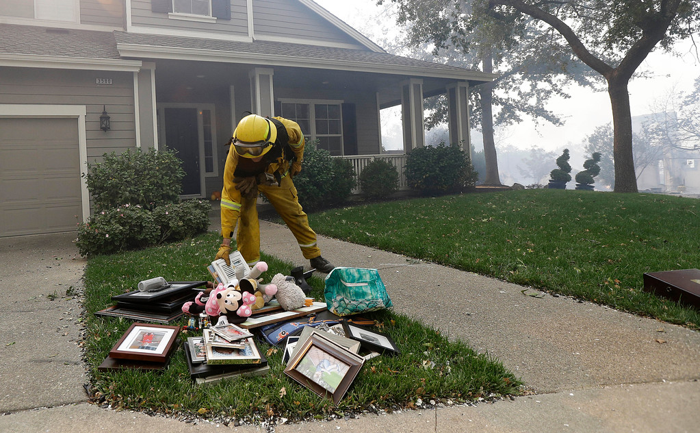 . A Santa Rosa firefighter places belongings onto the lawn of a home in Santa Rosa, Calif., Monday, Oct. 9, 2017. Wildfires whipped by powerful winds swept through Northern California, sending residents on a headlong flight to safety through smoke and flames as homes burned. (AP Photo/Jeff Chiu)