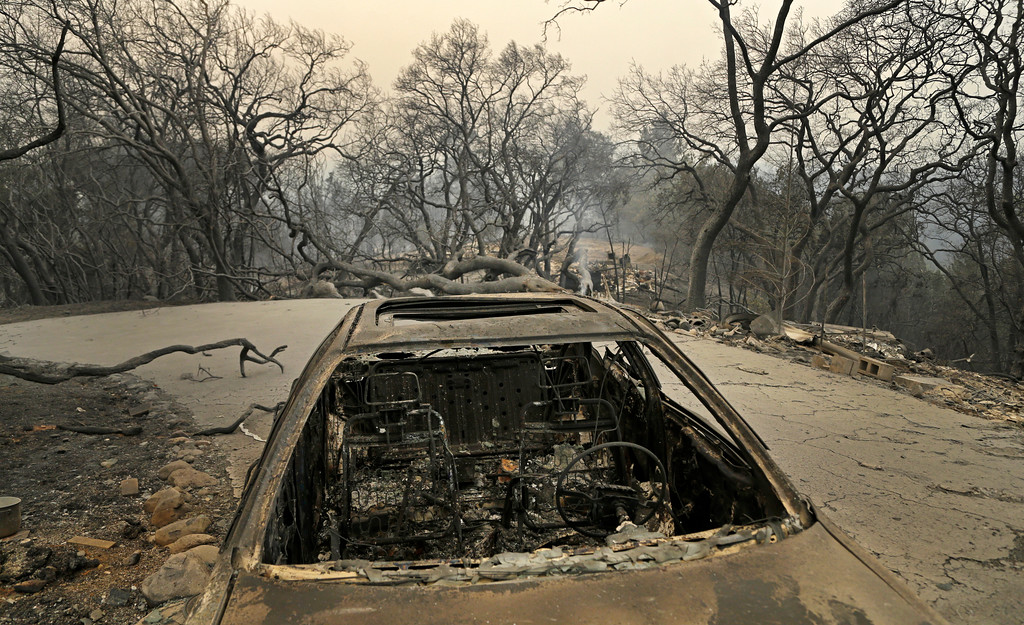 . Remains of a car seen Monday, Oct. 9, 2017, on Crystal Road in Santa Rosa, Calif. Wildfires whipped by powerful winds swept through Northern California early Monday, sending residents on a headlong flight to safety through smoke and flames as homes burned. (AP Photo/Ben Margot)