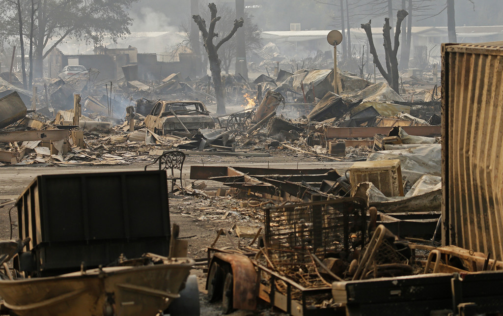 . Cars sit among the debris at the Journey\'s End mobile home park on Monday, Oct. 9, 2017, in Santa Rosa, Calif. Wildfires whipped by powerful winds swept through Northern California early Monday, sending residents on a headlong flight to safety through smoke and flames as homes burned. (AP Photo/Ben Margot)