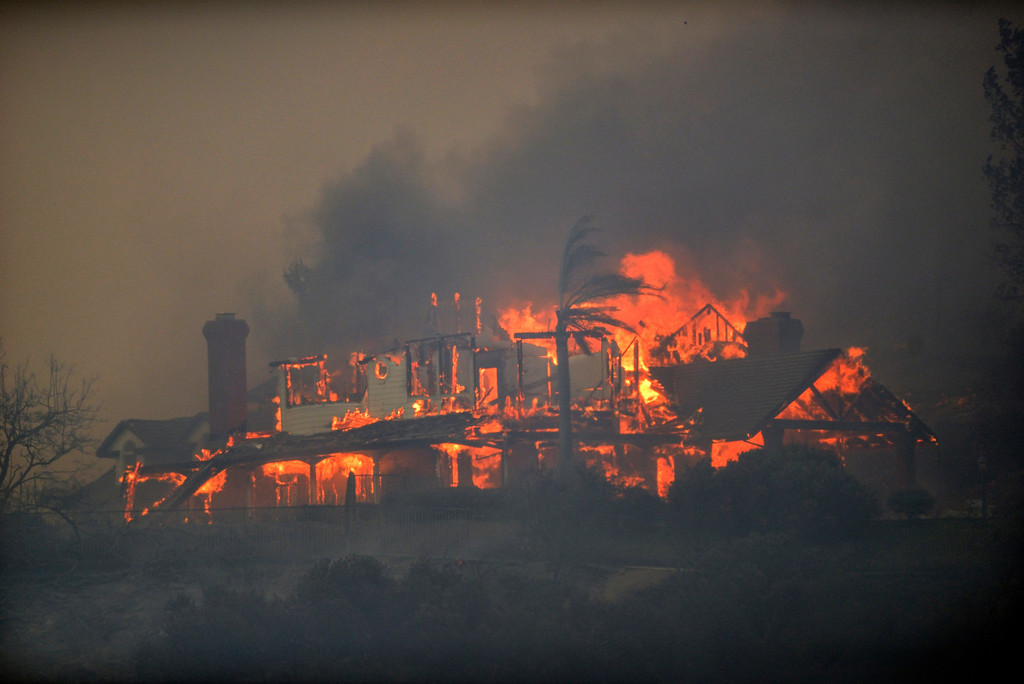 . A house is engulfed in flames from a wildfire in Anaheim Hills, Calif., Monday, Oct. 9, 2017. Wildfires whipped by powerful winds swept through Northern California sending residents on a headlong flight to safety through smoke and flames as homes burned. (Jeff Gritchen/The Orange County Register via AP)