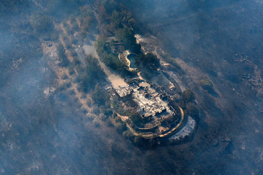 . Smoke rises from a home that was destroyed by a wildfire near Monticello Road in the hills east of Napa, Calif. Monday, Oct. 9, 2017. Wildfires whipped by powerful winds swept through Northern California sending residents on a headlong flight to safety through smoke and flames as homes burned. (Michael Short/San Francisco Chronicle via AP)