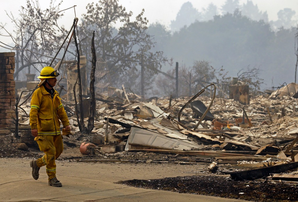 . A fireman looks for hotspots in the Fountaingrove area on Monday, Oct. 9, 2017, in Santa Rosa, Calif. Wildfires whipped by powerful winds swept through Northern California early Monday, sending residents on a headlong flight to safety through smoke and flames as homes burned. (AP Photo/Ben Margot)
