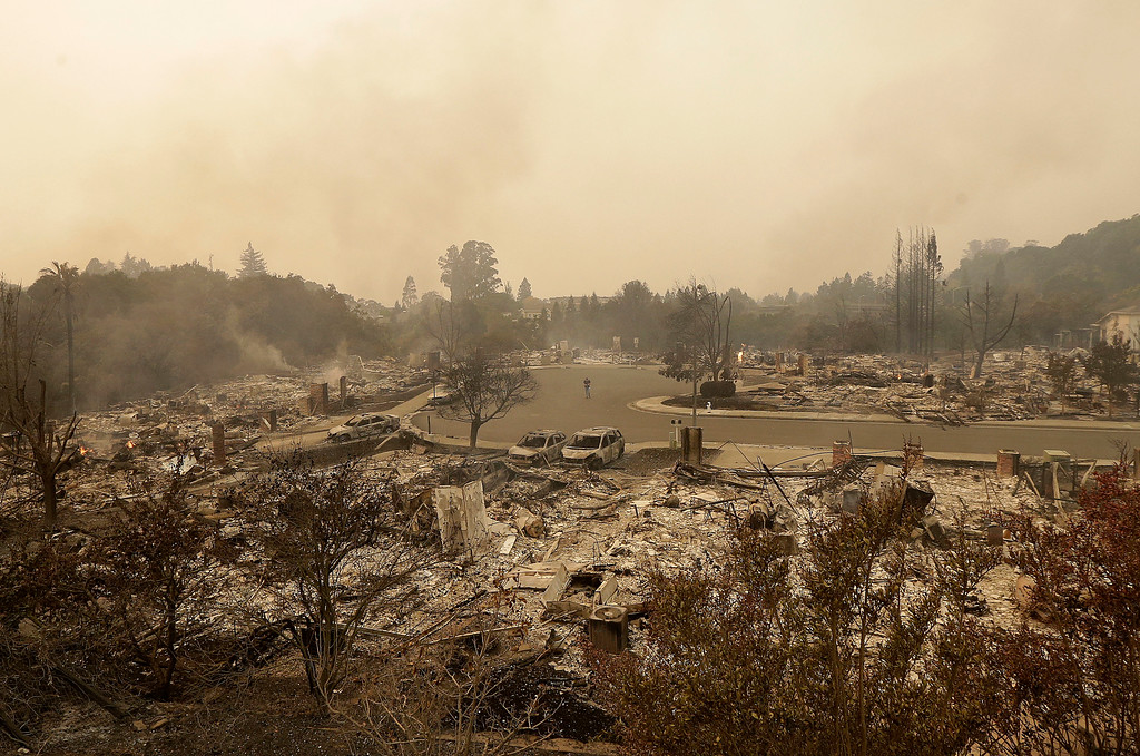 . A man walks down a street between the wreckage of houses destroyed by fire in Santa Rosa, Calif., Monday, Oct. 9, 2017. (AP Photo/Jeff Chiu)