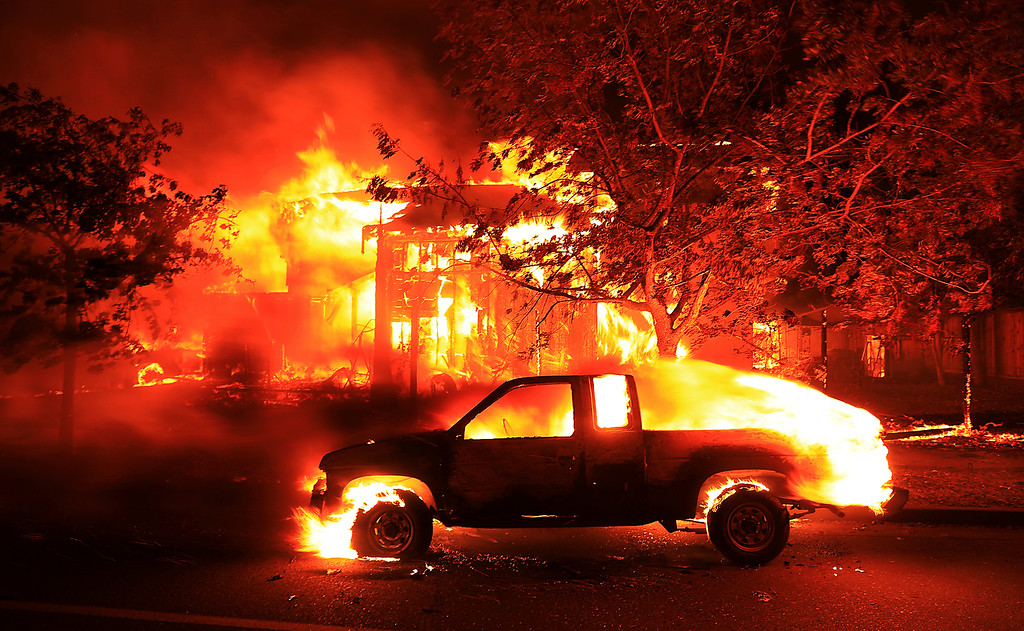 . Coffey Park homes burn early Monday Oct. 9, 2017 in Santa Rosa, Calif. More than a dozen wildfires whipped by powerful winds been burning though California wine country. The flames have destroyed at least 1,500 homes and businesses and sent thousands of people fleeing. (Kent Porter/The Press Democrat via AP)