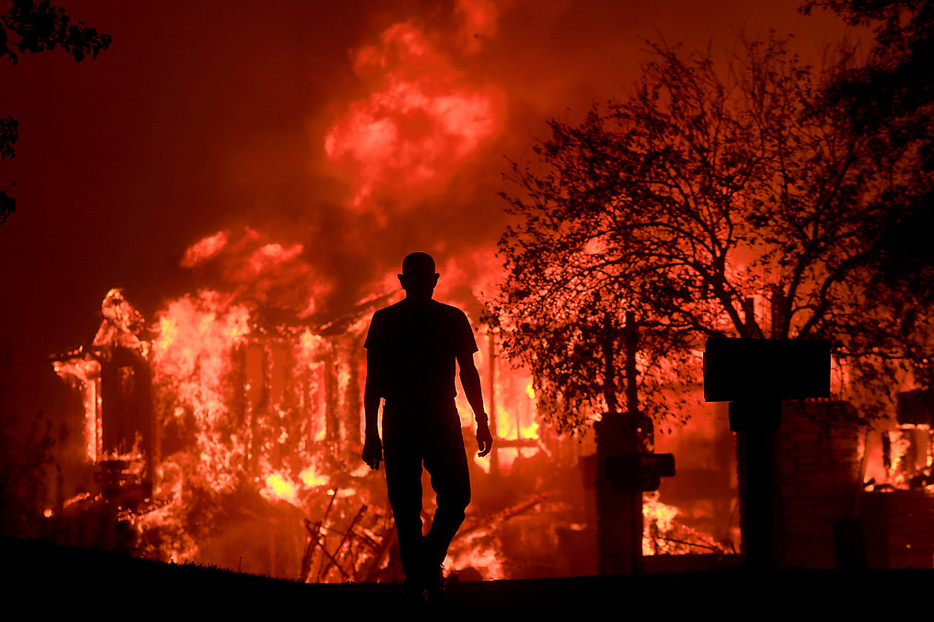. Jim Stites watches part of his neighborhood burn in Fountaingrove, Calif., Monday Oct. 9, 2017. More than a dozen wildfires whipped by powerful winds been burning though California wine country. The flames have destroyed at least 1,500 homes and businesses and sent thousands of people fleeing. (Kent Porter/The Press Democrat via AP)