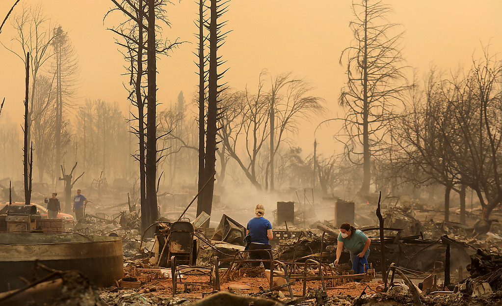 . Residents of the Coffey Park neighborhood sift through a relatives home that was torched, Monday, Oct. 9, 2017 in Santa Rosa. More than a dozen wildfires whipped by powerful winds been burning though California wine country. The flames have destroyed at least 1,500 homes and businesses and sent thousands of people fleeing. (Kent Porter/The Press Democrat via AP)