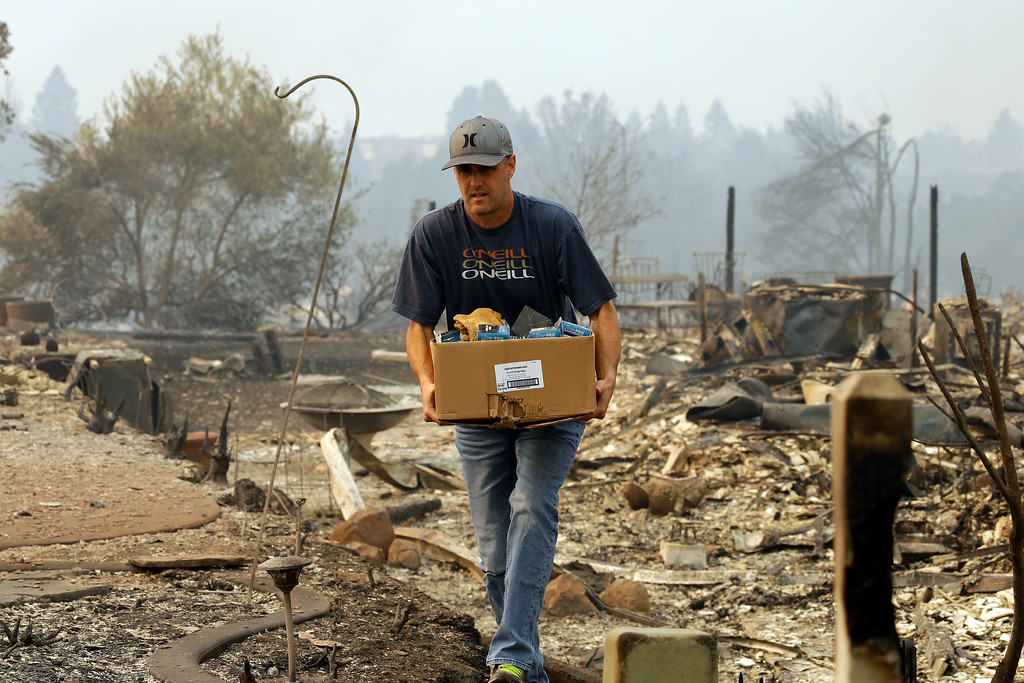 . A man retrieves belongings from a safe where his house once stood in the Fountaingrove area of Santa Rosa, Calif., on Monday, Oct. 9, 2017. Wildfires whipped by powerful winds swept through Northern California early Monday, sending residents on a headlong flight to safety through smoke and flames as homes burned. (AP Photo/Ben Margot)