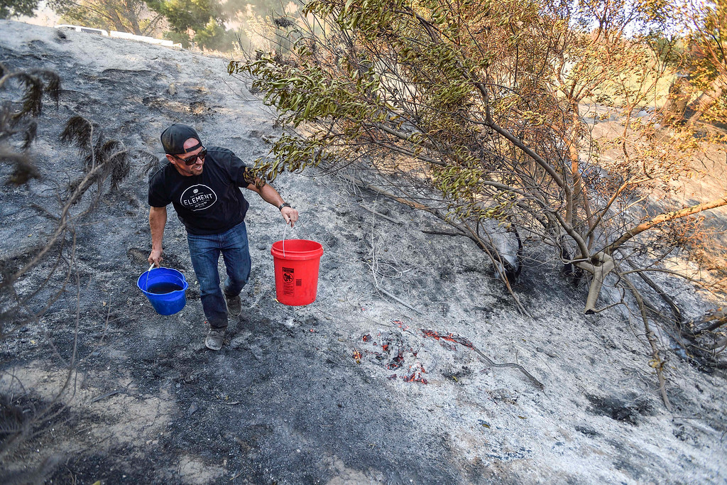 . Brandon Zimprich looks for hot spots as he walks along the hillside off East Avenida de Santiago in Anaheim, Calif., Monday, Oct. 9, 2017. Wildfires whipped by powerful winds swept through Northern California sending resident on a headlong flight to safety through smoke and flames as homes burned. Zimprich lives in the neighborhood and said he was trying to help the firefighters. (Jeff Gritchen/The Orange County Register via AP)