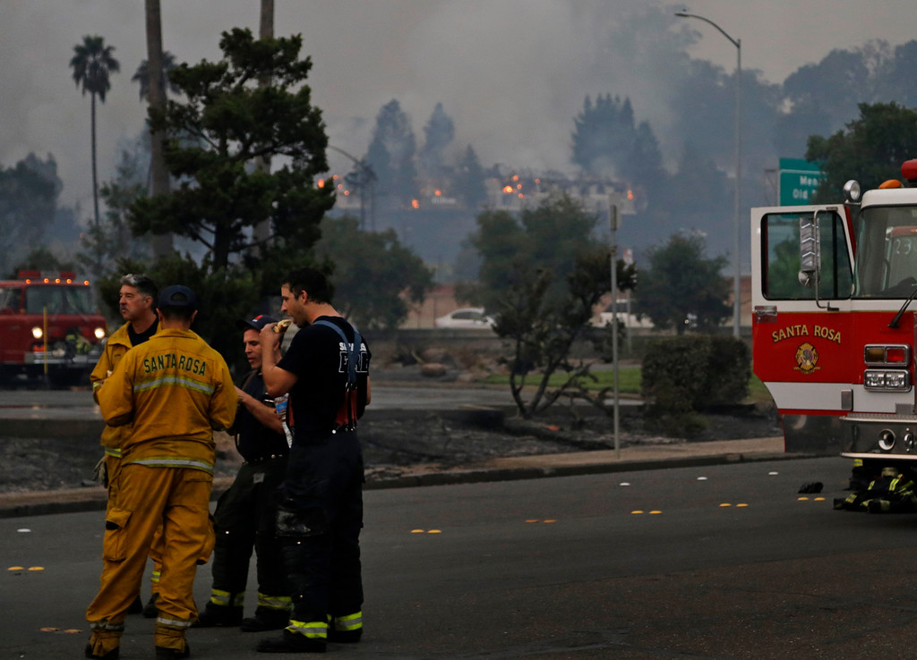 . Santa Rosa firemen take a break from fighting a business fire as the Hilton hotel continues to burn in the background on Monday, Oct. 9, 2017, in Santa Rosa, Calif. Wildfires whipped by powerful winds swept through Northern California early Monday, sending residents on a headlong flight to safety through smoke and flames as homes burned. (AP Photo/Ben Margot)