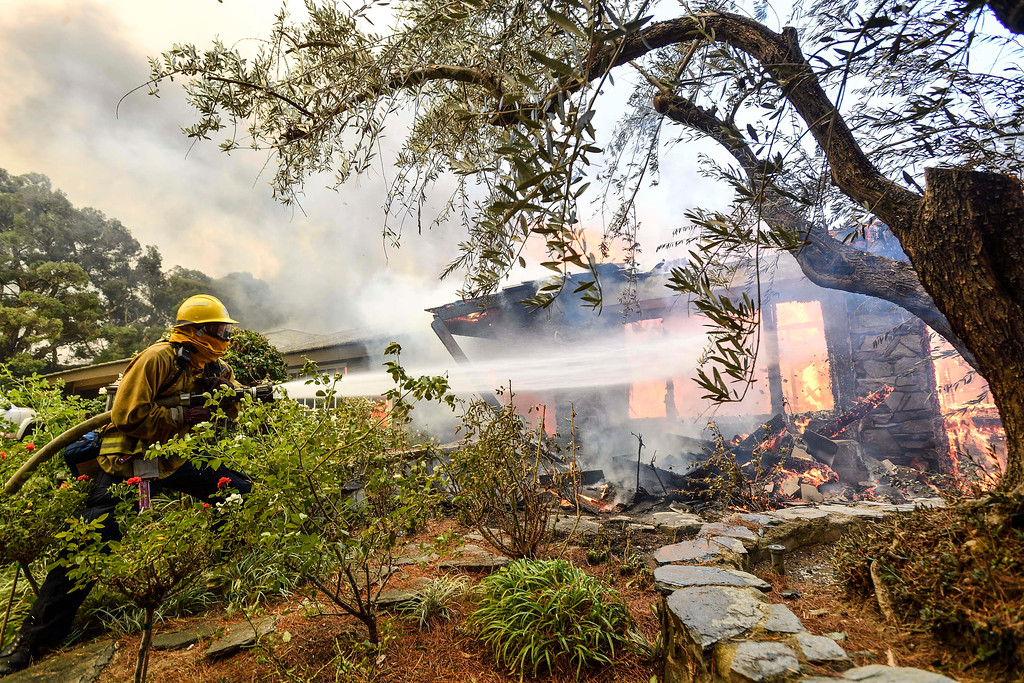 . Firefighters work to extinguish flames from a wildfire in Anaheim Hills, Calif., Monday, Oct. 9, 2017. Wildfires whipped by powerful winds swept through Northern California sending residents on a headlong flight to safety through smoke and flames as homes burned. (Jeff Gritchen/The Orange County Register via AP)