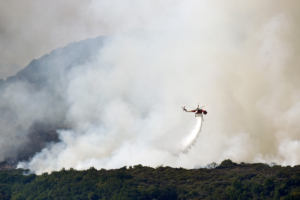 . A helicopter drops water as a wildfire burns in the hills east of Napa, Calif., Monday, Oct. 9, 2017. Wildfires whipped by powerful winds swept through Northern California sending residents on a headlong flight to safety through smoke and flames as homes burned. (Michael Short/San Francisco Chronicle via AP)