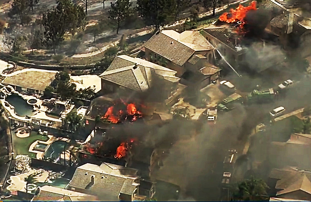. In this image made from a video provided by KABC-TV, a fire burns in the Anaheim Hills area of Anaheim, Calif., in northern Orange County in Southern California on Monday, Oct. 9, 2017. Wildfires whipped by powerful winds swept through Northern California sending residents on a headlong flight to safety through smoke and flames as homes burned. (KABC-TV via AP)