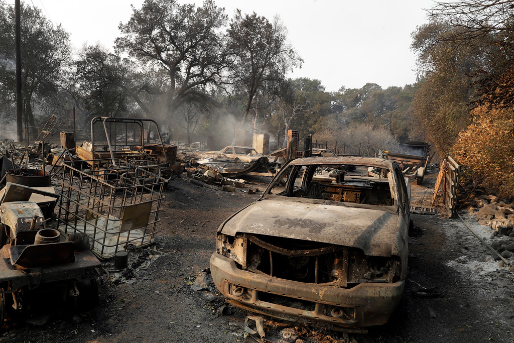 . Burned out vehicles are parked in front of a fire-ravaged home Monday, Oct. 9, 2017, in Napa, Calif. Wildfires whipped by powerful winds swept through Northern California sending residents on a headlong flight to safety through smoke and flames as homes burned. (AP Photo/Marcio Jose Sanchez)